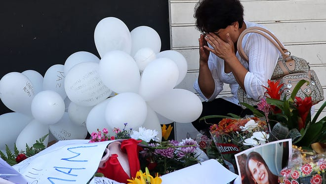 A woman visits a makeshift memorial in front of the Kiss nightclub in Santa Maria, Brazil, on Tuesday.