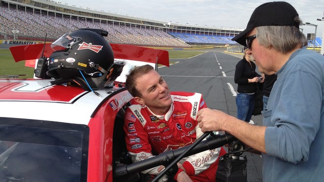 Kevin Harvick talks with a production shoot crewman while taking a break from filming footage for Budweiser's 360-degree view mobile app.