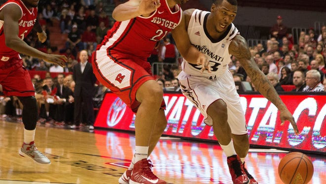 Cincinnati guard Sean Kilpatrick drives on Rutgers forward Austin Johnson during the first half of the game at the Fifth Third Arena. The Bearcats won 62-54.