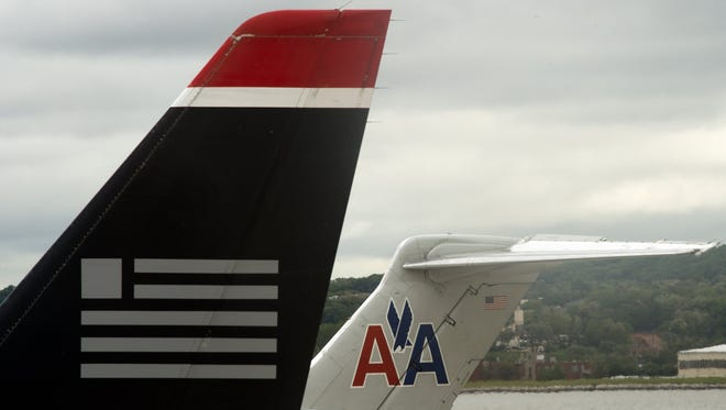 The tails of American Airlines and US Airways aircraft are seen at Ronald Reagan Washington National Airport on April 23, 2012.