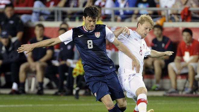 The USA's Brad Evans, left, and Canada's Kyle Bekker vie for the ball during the first half of a 0-0 draw Tuesday in Houston.