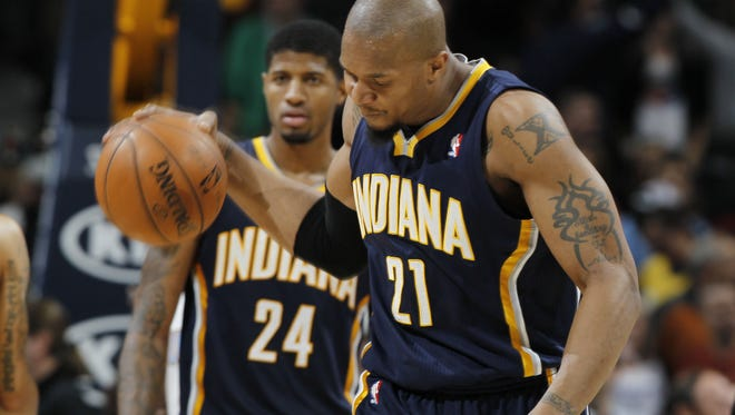 Indiana Pacers forward David West, front, slams the ball on the court as forward Paul George looks on after the Denver Nuggets' 102-101 victory over the Pacers in Denver.