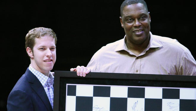 Former Pistons player Rick Mahorn presents Sprint Cup champion Brad Keselowski with an honorary checkered flag during halftime of the game between Detroit and Milwaukee on Jan. 29.