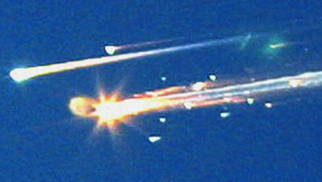 Debris from the space shuttle Columbia streaks across the sky over Tyler, Texas. Feb. 1, 2003.