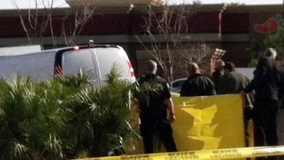 Arizona officials check a body Jan. 31 that a landscaper found in bushes a Mesa, Ariz., shopping center. Officials think Arthur D. Harmon died of a self-inflicted gunshot wound. He is accused of shooting three others in an office complex that day before.