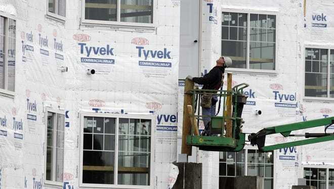 A construction worker inspects the vapor barrier on a home being built Jan. 11 in Chicago.