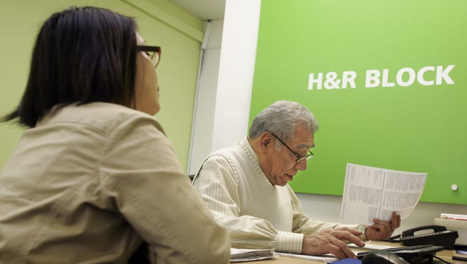 H&R Block senior tax advisor Bacho Medina, right, helps JoAn Ramos with her taxes at an H&R Block office in San Francisco, Monday, April 16, 2007.
