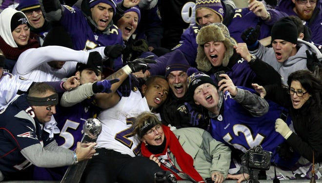 Ravens running back Ray Rice celebrates with fans in the stands after the AFC championship game against the Patriots.  The Ravens won 28-13.