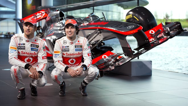 Jenson Button, left, and Sergio Checo Perez pose for pictures with the new McLaren Mercedes MP4-28 Formula One car that will be unveiled in the 2013 season.