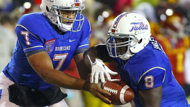 Tulsa quarterback Cody Green (7) hands the ball off to running back Alex Singleton (8) in the Liberty Bowl in December. Tulsa, which won 31-17, is said to be in leading contention to be the Big East's 12th member.