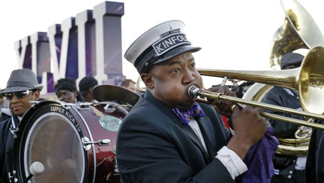 Richard Anderson, of New Orleans, plays the trombone as the Kinfolks Brass Band marches along the Riverwalk in New Orleans on Friday. The Baltimore Ravens will play the San Francisco 49ers in the NFL football Super Bowl on Sunday.