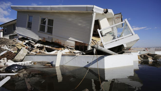 A storm-damaged beachfront house is reflected in a pool of water in Queens, N.Y.