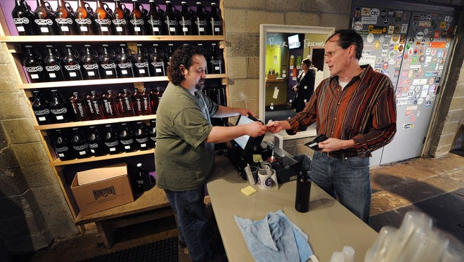 Max Scott sells beer to Tom Hudson at Flat 12 Bierworks this month in Indianapolis. Indiana is the toughest state in the nation to find a drink on a Sunday.