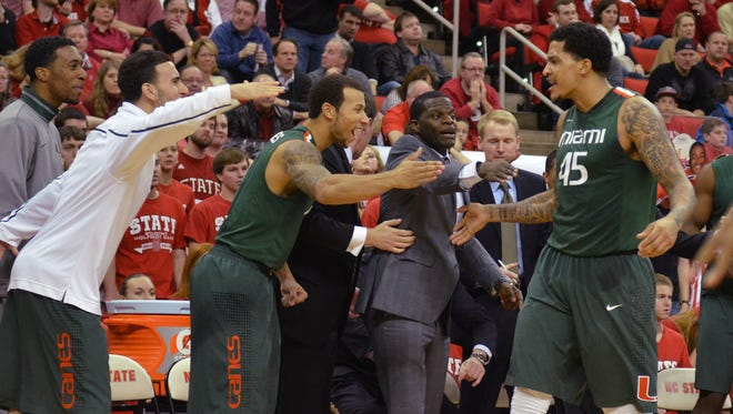 Miami forward Julian Gamble (45) receives congratulations from teammates after a second half basket against the North Carolina State Wolfpack on Saturday.  Miami won 79-78.