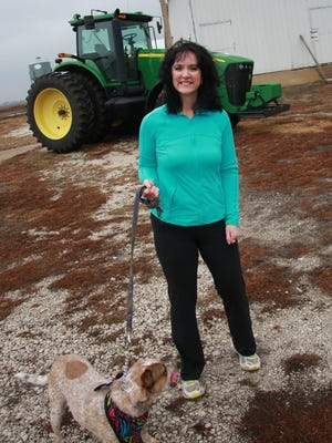 "Darcy Maulsby, 39, walks her dog Maggie on her Century Farm between Lake City and Yetter, Iowa, in January. She writes ""Farmerlicious,"" a blog that features easy, healthy recipes from her farm kitchen and shares interesting farm-to-fork tidbits."