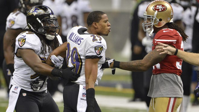 Baltimore Ravens outside linebacker Paul Kruger (99) holds back cornerback Cary Williams (29) as he talks to San Francisco 49ers free safety Dashon Goldson (38) during the second quarter in Super Bowl XLVII at the Mercedes-Benz Superdome.