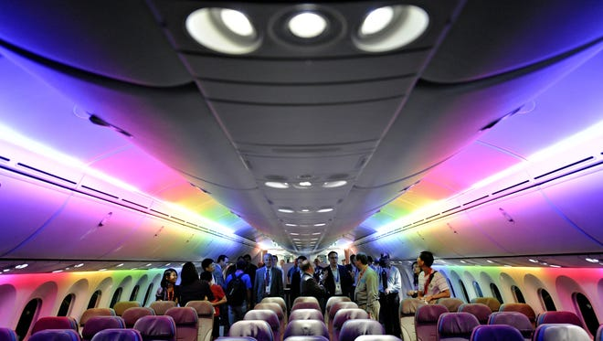 Members of the media tour Boeing 787 Dreamliner's cabin displaying versatile LED lighting system during a press preview in Singapore.
