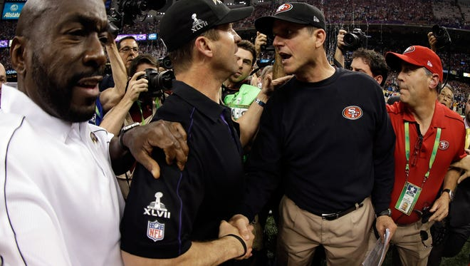Ravens coach John Harbaugh , left, shakes hands with his brother  Jim, the head coach of the 49ers, after Baltimore won Super Bowl XLVII Sunday,