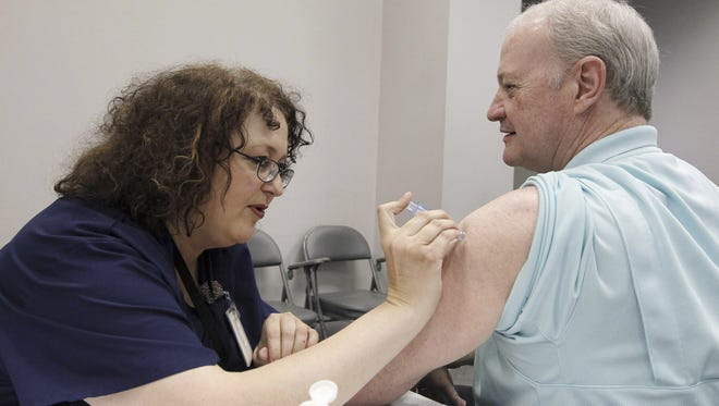 Nurse Rosemary Jones vaccinates Bill Staples of the Mississippi health agency.