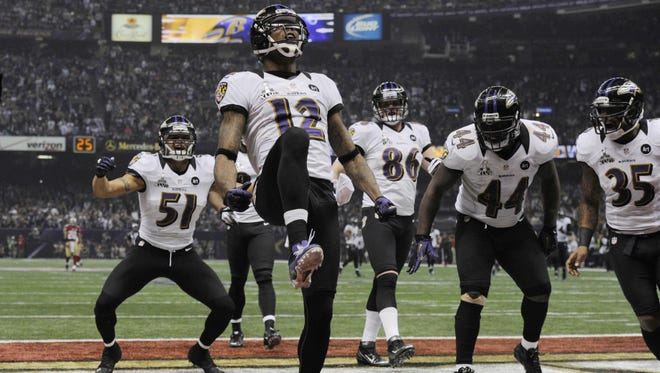 Baltimore Ravens wide receiver Jacoby Jones (12) celebrates with teammates after returning a kick for a touchdown against the San Francisco 49ers in the third quarter in Super Bowl XLVII.