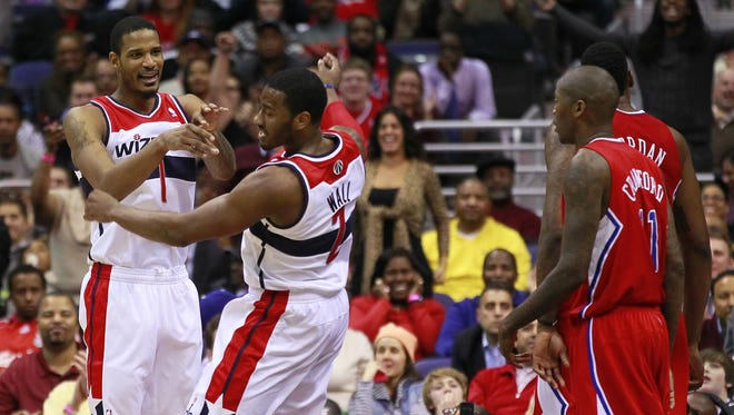 Washington Wizards point guard John Wall celebrates with Wizards small forward Trevor Ariza against the Los Angeles Clippers in the fourth quarter at Verizon Center.