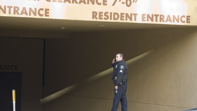 An Irvine police officer talks on the phone Monday at the entrance to the parking garage where two people were found shot to death in their car in Irvine, Calif. Police in Orange County say they have no motive for a shooting that killed California State University Fullerton assistant college basketball coach Monica Quan and her fiance, Keith Lawrence.