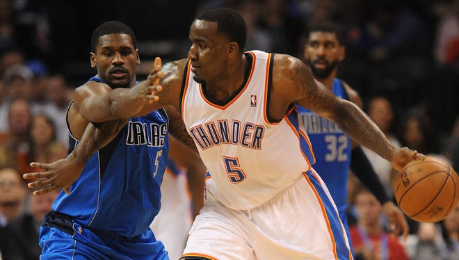 Oklahoma City Thunder center Kendrick Perkins (5) handles the ball against Dallas Mavericks center Bernard James (5) during the first half at the Chesapeake Energy Arena.