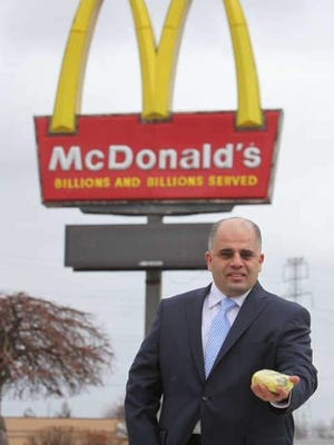 Dearborn, Mich., attorney Majed Moughni, holding a McChicken sandwich at McDonald's on Ford Road in Dearborn, says a settlement reached Jan. 7 enriches others at the expense of people who mistakenly ate non-halal meat.