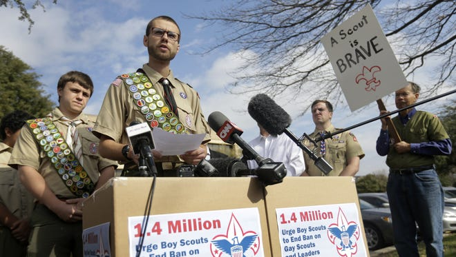 James Oliver, left, stands behind his brother and fellow Eagle Scout, Will Oliver, who is gay, as he makes comments during a news conference in front of the Boy Scouts of America headquarters on  Monday.