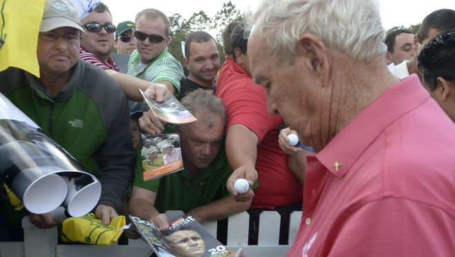Fans crowd the fence outside the 18th green to get autographs from Arnold Palmer at the Father-Son Challenge in December.