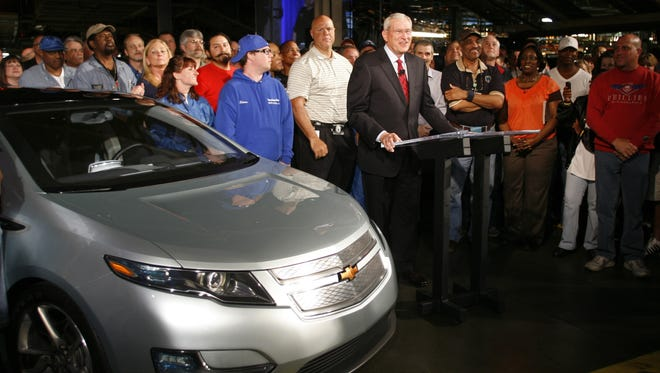 Then-General Motors CEO Edward Whitacre Jstands with workers and a new Chevrolet Volt as he announces repayment of loans during a news conference at the GM Fairfax plant Wednesday, April 21, 2010,