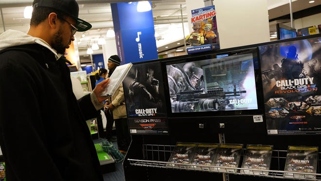 NEW YORK, NY - JANUARY 11:  A  man looks at a copy of the game Call of Duty Black Ops 2 at an electronics store on January 11, 2013 in New York City.  Following the shootings of children at a elementary school last month in Connecticut, numerous politicians and activists have begun to focus on violence in video games and films. US vice-president Joe Biden is meeting with games industry representatives today to discuss graphic violence, often with guns, in many of today's most popular video games.  The administration is also expected to address violence in the film industry as well. (Photo by Spencer Platt/Getty Images) ORG XMIT: 159452861 ORIG FILE ID: 159313967