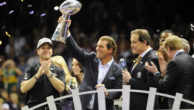 Baltimore Ravens owner Steve Bisciotti hoists the Vince Lombardi Trophy after defeating the San Francisco 49ers in Super Bowl XLVII. On his right is coach John Harbaugh.