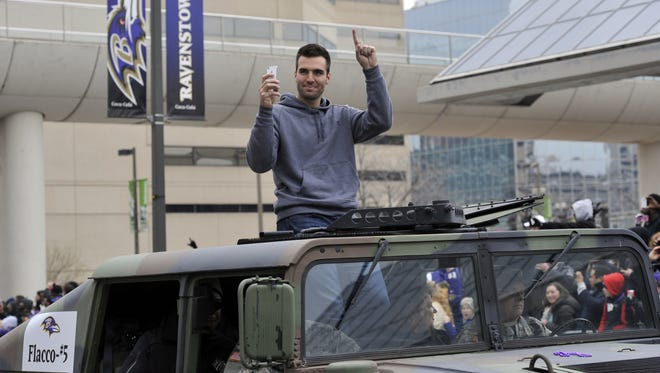 Super Bowl XLVII MVP rides in a Humvee in Baltimore's downtown parade for the Ravens on Tuesday.