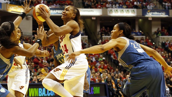 Indiana Fever forward Tamika Catchings (24) drives to the basket against Minnesota Lynx forward Maya Moore (23) during the WNBA Finals at Bankers Life Fieldhouse.