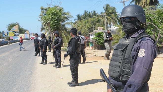 Mexican state police stand at a roadblock Feb. 5 that was set up after masked armed men broke into a beach home, raping six Spanish tourists who had rented the house in Acapulco, Mexico.