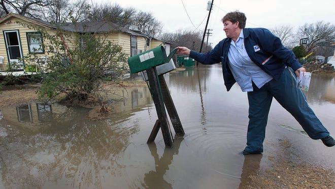 United States Postal employee Sue Stokes tip toes into a small pool of water as she delivers the mail to an area resident in Bellmead, Texas.