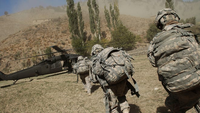 U.S. soldiers race toward a Blackhawk helicopter as they are picked up from a mission in Paktika Province, Afghanistan.  in 2009.