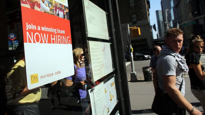 A sign in a cafe window advertises employment opportunities in New York City.