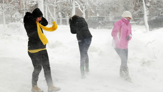 People cover their faces as winds whip the snow in Boston.