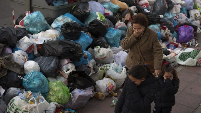 A woman and children cover their noses as they walk past rubbish bags piled up next to overflowing garbage containers in Seville, Spain.