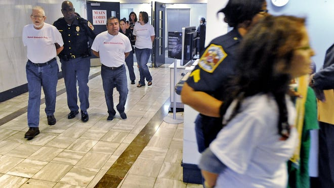 Protesters of Alabama's controversial immigration law sing as they are detained by State Capitol Police after a sit-down protest outside of the Senate chamber in the Alabama Statehouse on Thursday, May 3, 2012.