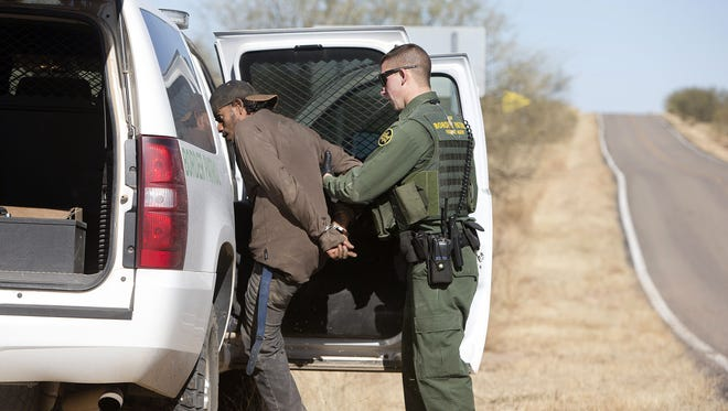 Border Patrol officers detain a suspected undocumented immigrant on Highway 286, between Sasabe and Arivaca, Ariz.