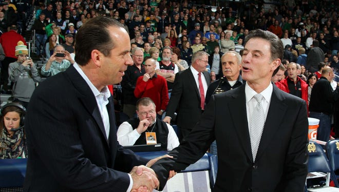 Louisville coach Rick Pitino, right, talks with Notre Dame coach Mike Brey before their teams' game Saturday.