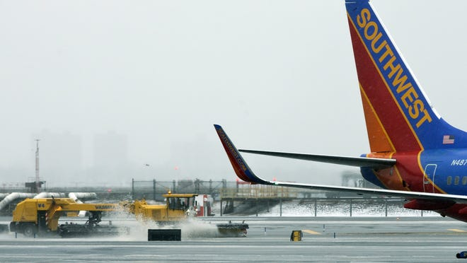 Grounds crews clear the runway as snow falls at LaGuardia Airport on Friday.