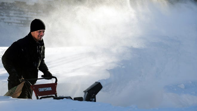 Tony Colon uses a snowblower to clear his driveway Saturday in Derby, Conn., where residents face massive snow removal.
