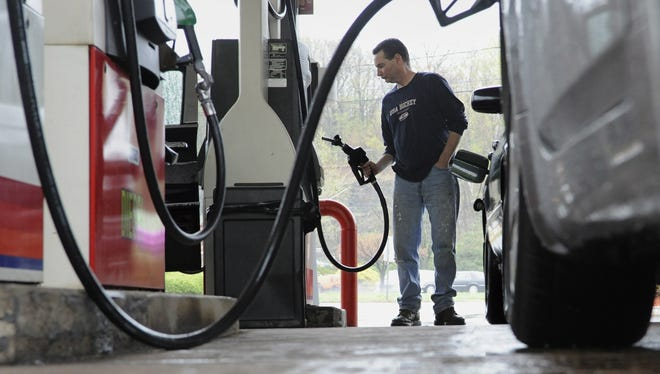 John Magel pumps gas at a station in Wethersfield, Conn. , in a 2011 file photo