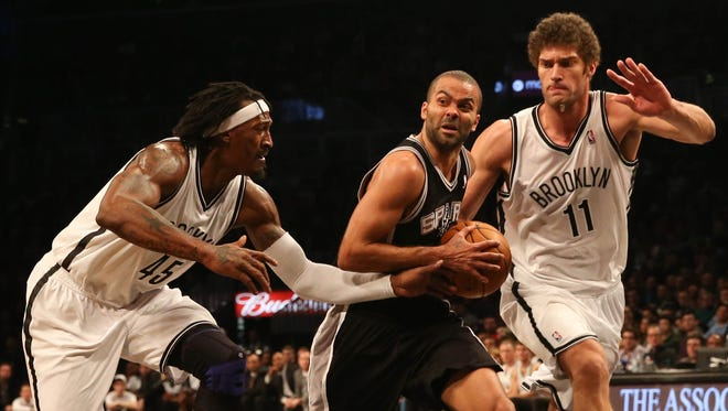 Spurs point guard Tony Parker drives between Nets forward Gerald Wallace, left, and center Brook Lopez during Sunday's 111-86 win.