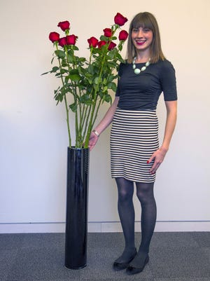 USA TODAY retail reporter Hadley Malcolm stands next to 5-foot -plus high long-stemmed roses on sale by flower company FTD for Valentine's Day.