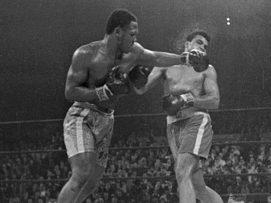 Muhammad Ali. right, takes a left from Joe Frazier during the 15th round of their heavyweight title boxing bout in New York in 1971. Frazier won a unanimous decision, Ali's first loss in the ring.